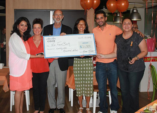 Cisco employees in Australia present a check for US$21,000 to the New South Wales Food Bank.