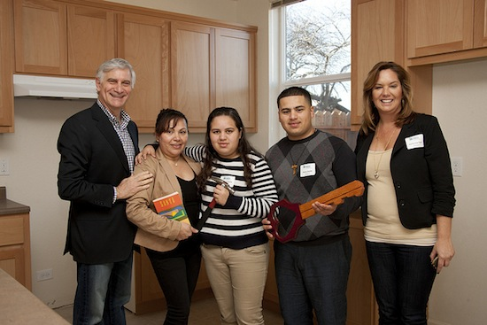 Cisco employees Steve Martino (left) and Katherine Toch (right) with the Zavala family in their new home.