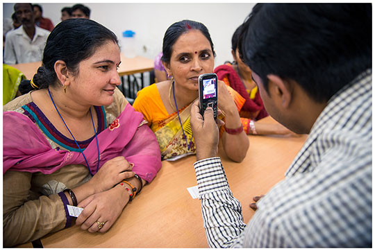 Trainers at a garment factory in India show workers how to use mobile phones to take anonymous surveys. Photo: Arjun Kartha