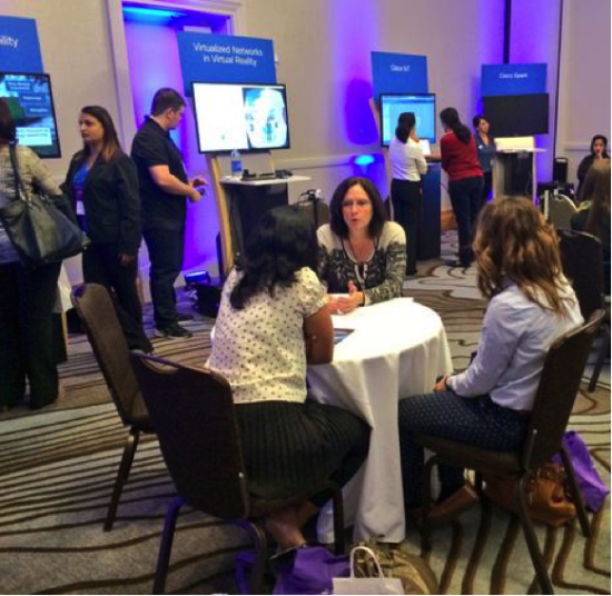 Rebecca Jacoby, Senior Vice President of Operations at Cisco, speaks with attendees about career development at Cisco's Innovation Café during the conference.