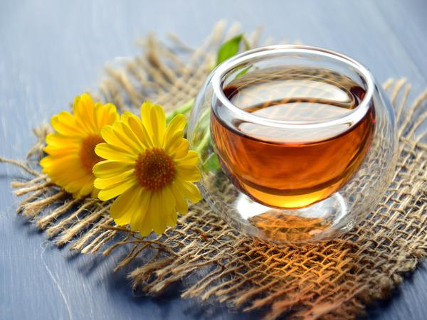 Glass cup of bee honey with yellow flowers.