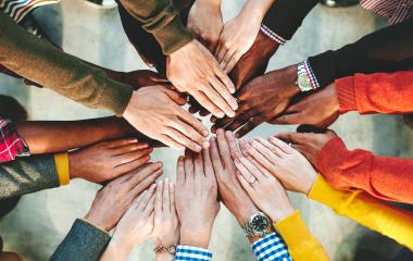 Grupo de pessoas diversas unindo as mãos.