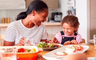Mãe e filha se divertem durante uma refeição saudável na cozinha.