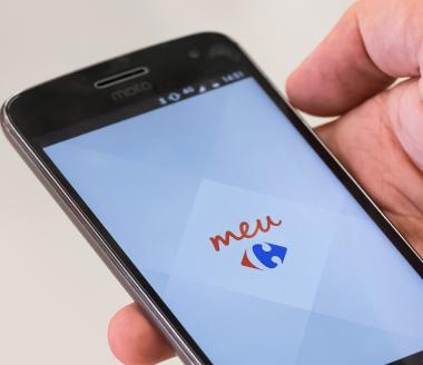 Mão exibe smartphone acessando o aplicativo Meu Carrefour.