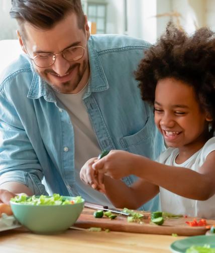 Família se diverte preparando uma refeição saudável.