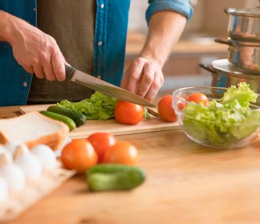 Homem preparando uma refeição saudável cortando legumes e verduras frescas.