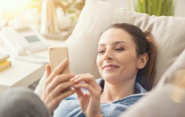 Mulher tranquila no conforto de casa utilizando smartphone.