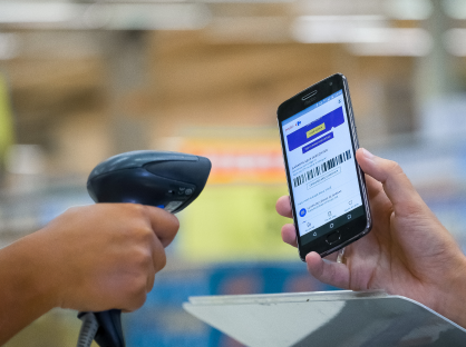 Atendente fazendo a leitura de código de barras do aplicativo Meu Carrefour direto no smartphone do consumidor.