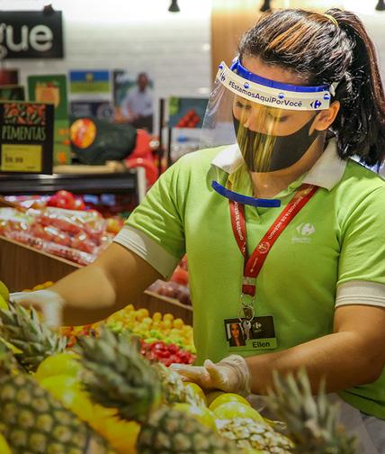 Colaboradora com protetor facial organiza a exposição das frutas usando luva no hipermercado Carrefour.