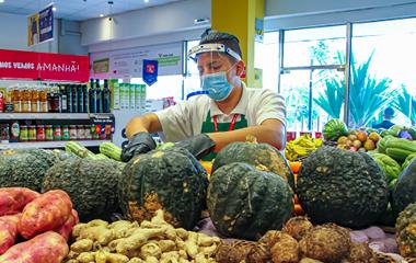 Colaborador do Carrefour Market organiza os legumes na loja.