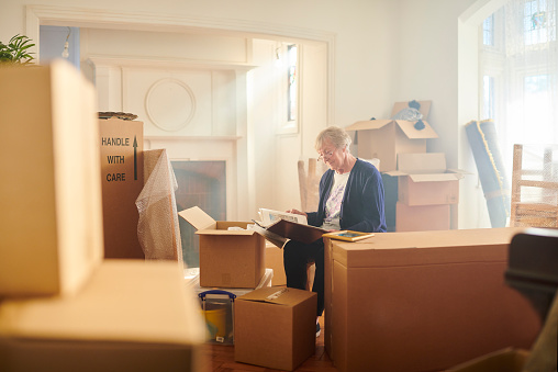 senior woman sitting in a room surrounded by moving boxes