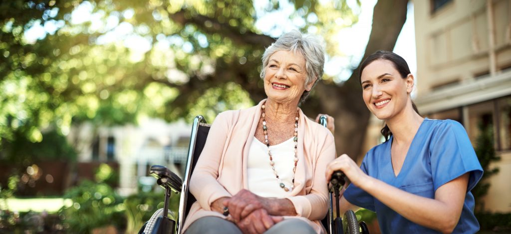 young nurse spending time with a senior woman in a wheelchair in the garden