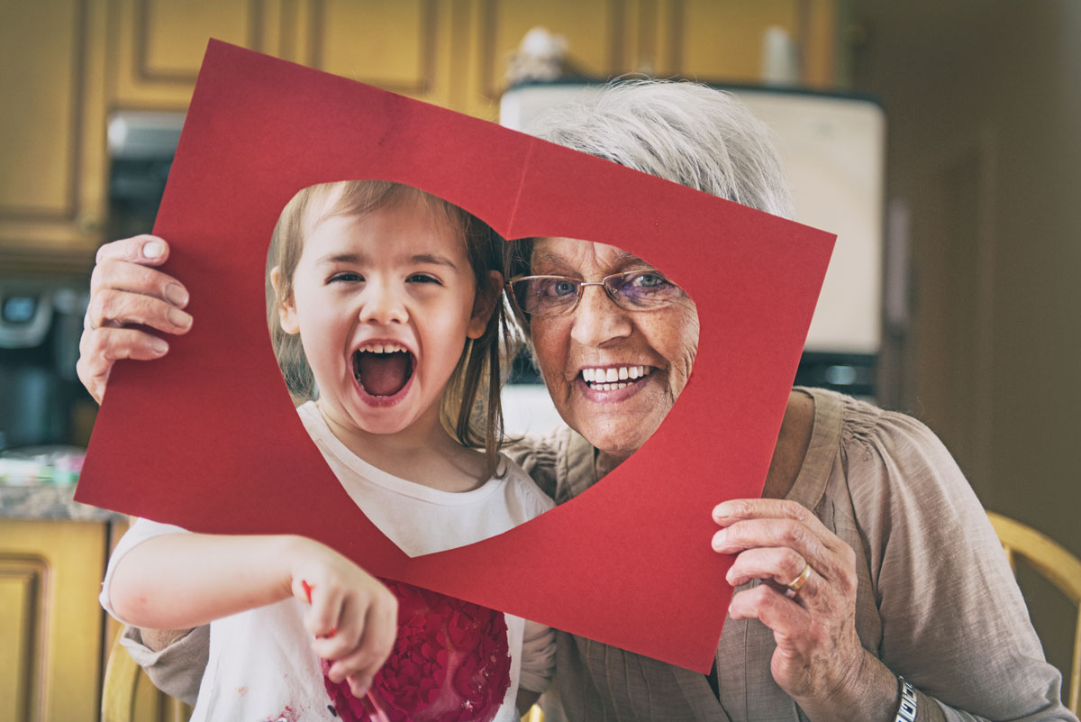 Grandmother and grandchild holding a cutout heart to their faces for a picture