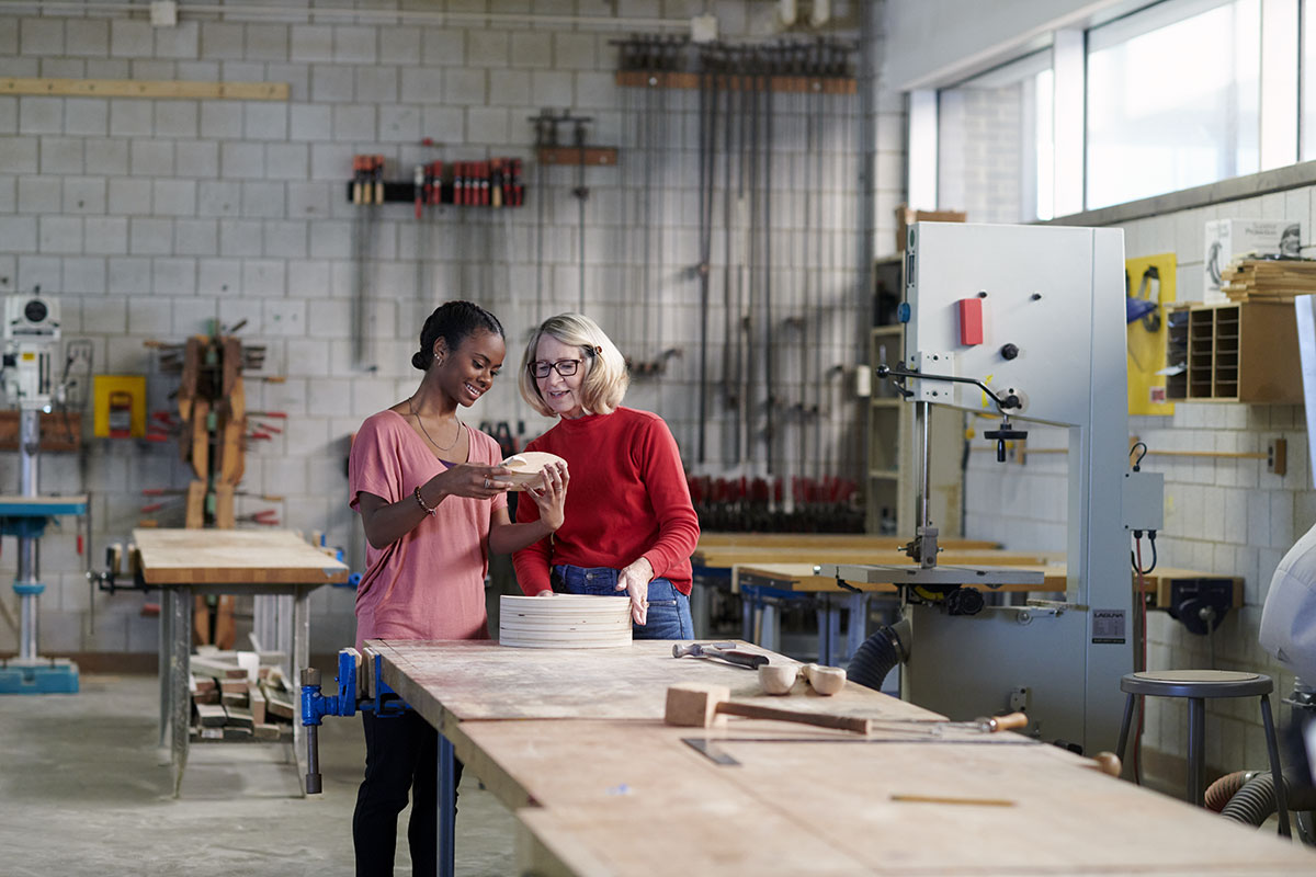 Senior and student taking a woodshop class