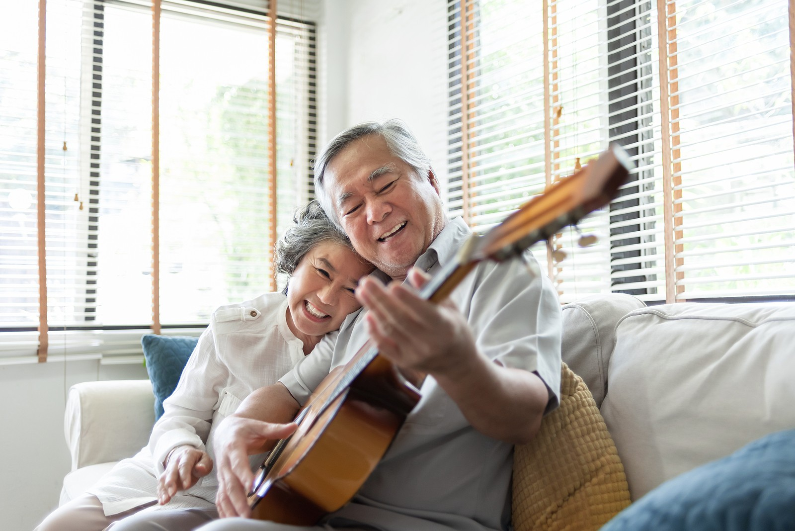 Happy senior couple listening and playing acoustic guitar together.