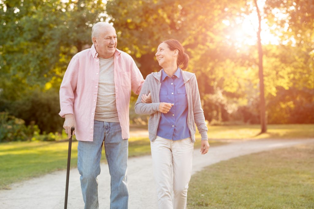 Senior man and caregiver go walking outdoors