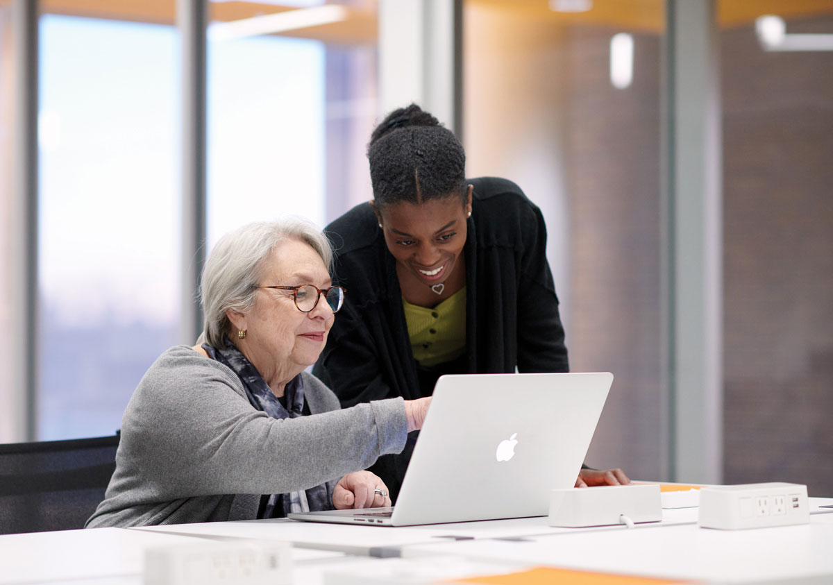 A young woman leans over a senior woman's shoulder to look at a laptop