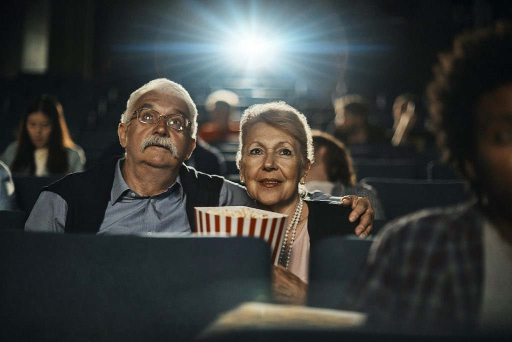 Close up of a senior couple captivated by a movie in the cinema