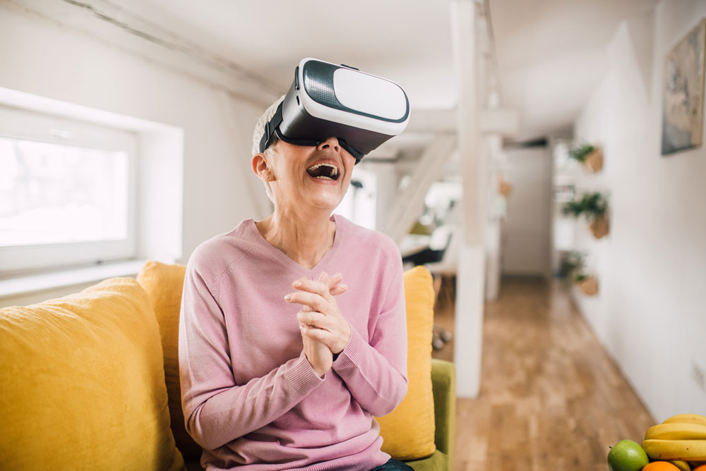 Woman demonstrates benefits of technology for seniors and uses virtual reality headset.