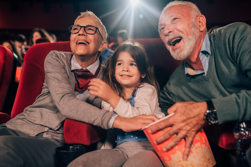 Multi-generation family watching a funny movie in the cinema