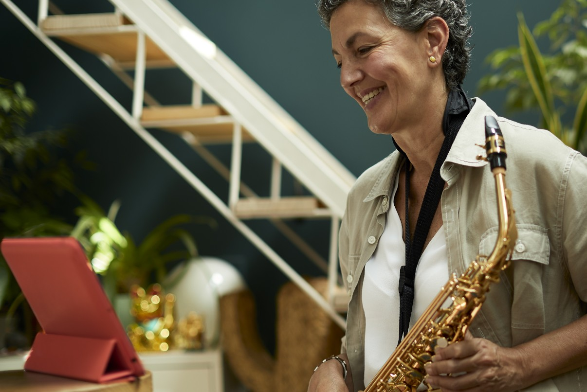 Senior woman learning to play the saxophone online