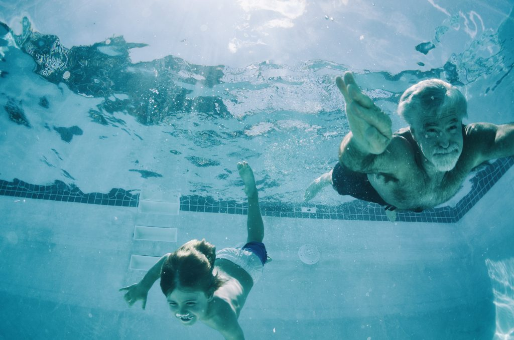 Grandpa and Grandson swimming underwater in pool in summer
