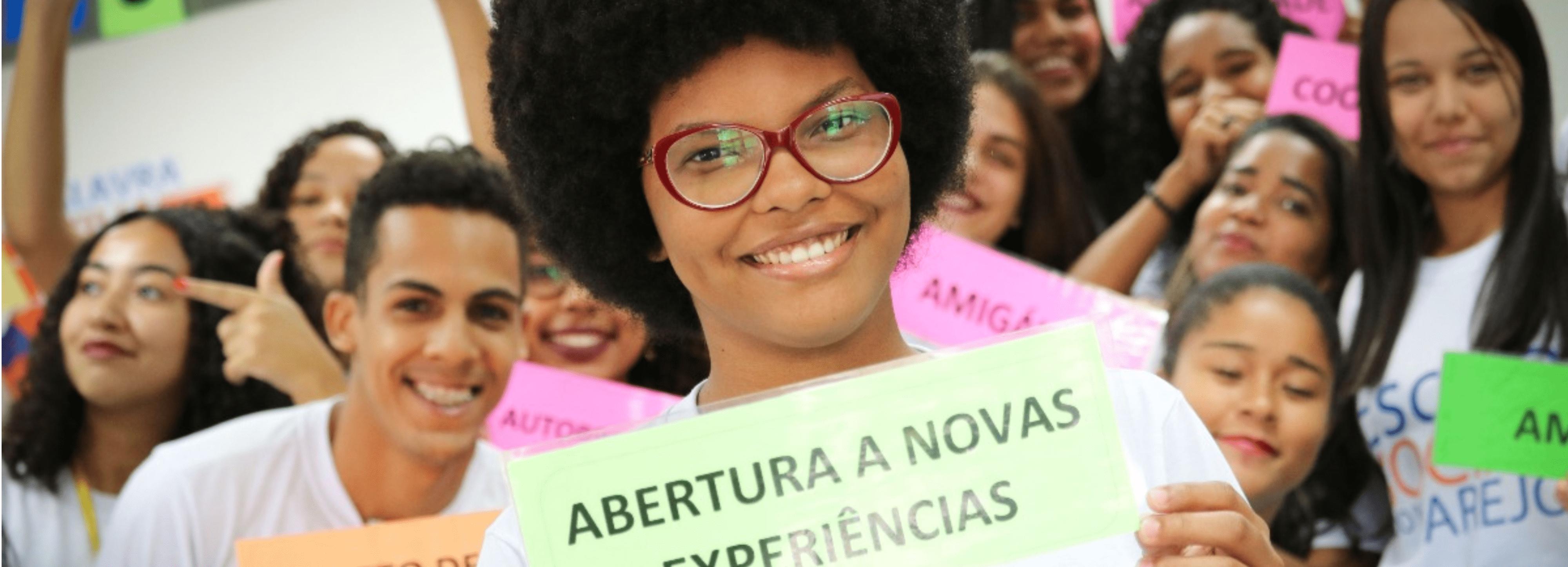 """Aluna da escola social do varejo segurando um placa com os dizeres """"Abertura a novas experiencias""""."""