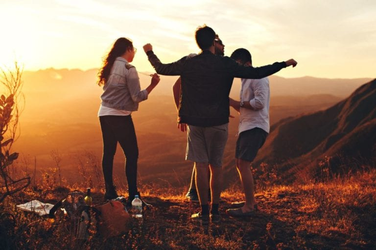 Three young adults enjoying a sunset outdoors in a mountainscape.