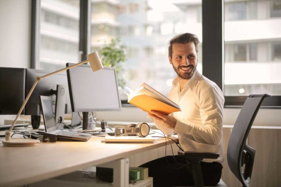A smiling male office worker sitting at a desk in a modern office.