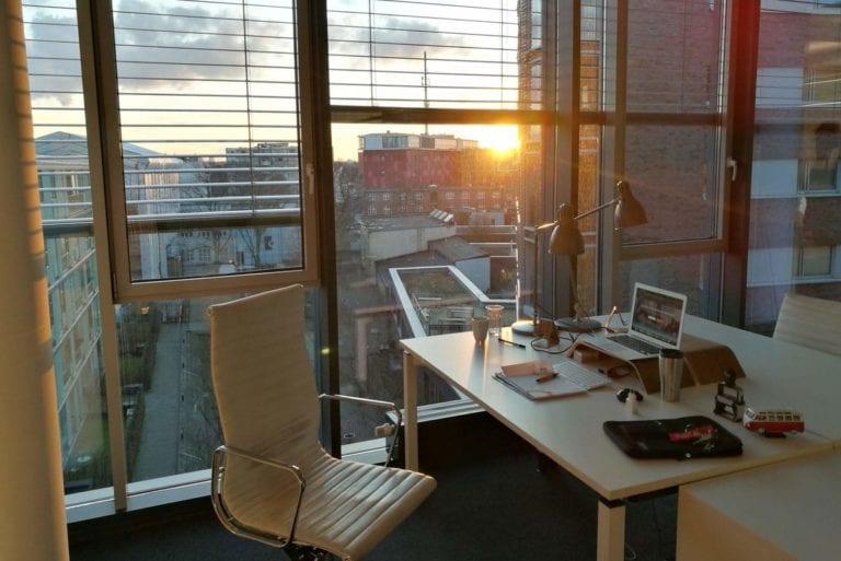 A sunset shining through the windows of a light modern office.