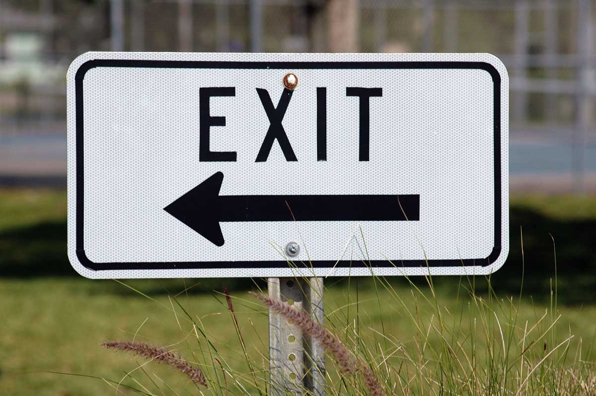 An exit road sign next to a green lawn.