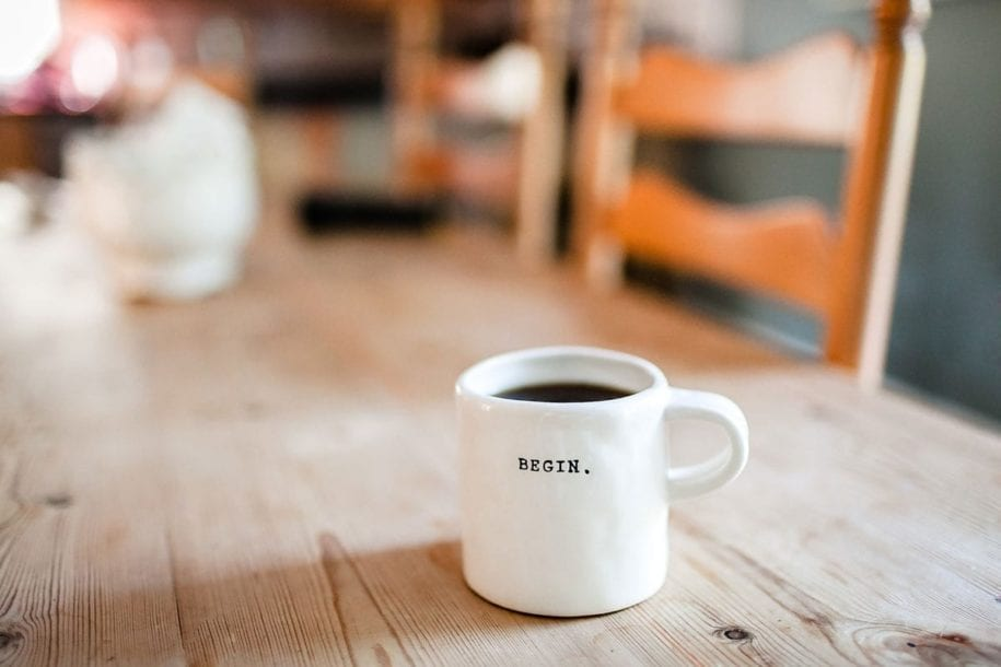 A full coffe cup with on a wooden table.