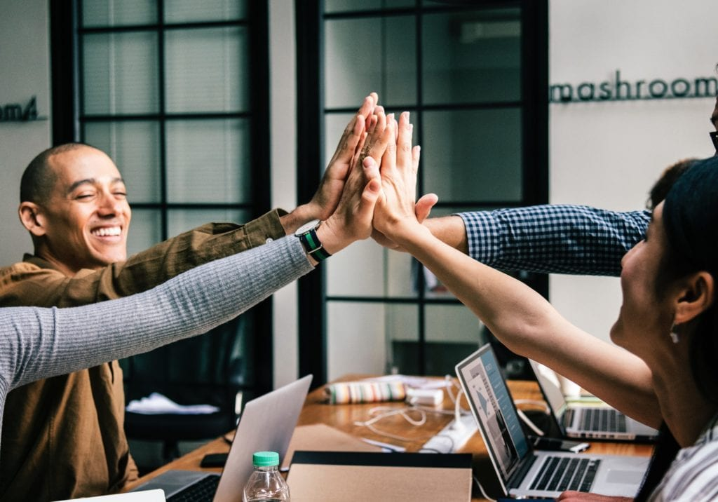 Four people in an office giving each other one join high five.