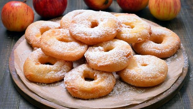 Pile of mini powdered sugar donuts against a white background