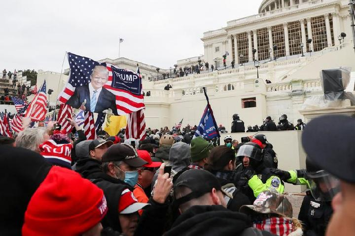Pendukung Presiden AS Donald Trump bentrok dengan petugas polisi di depan Gedung Capitol AS di Washington, AS, 6 Januari 2021. [REUTERS / Leah Millis]
