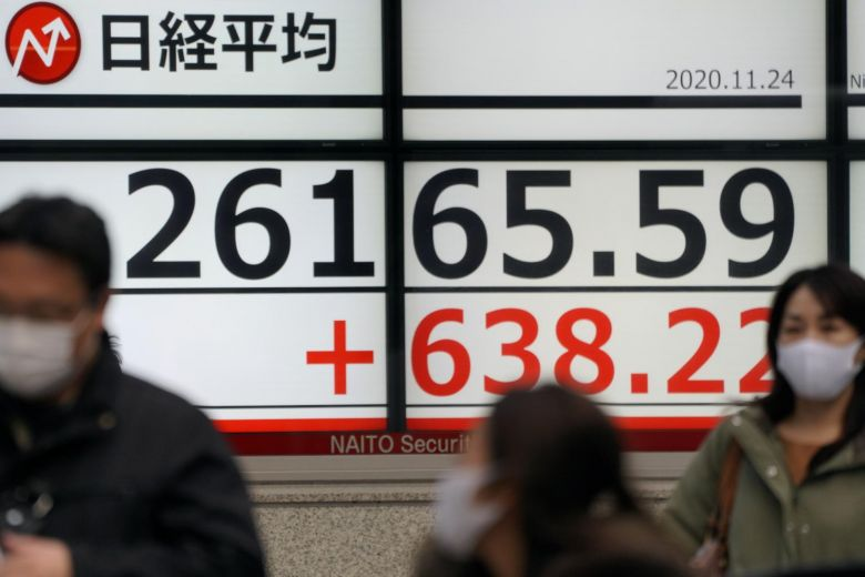 Pedestrians walk past a display showing closing information of the Nikkei Stock Average in Tokyo, Japan, 24 November 2020.