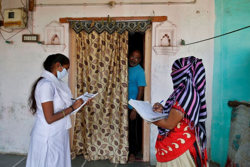 Health workers collect personal data from a man ahead of a Covid-19 vaccine rollout in a village on the outskirts of Ahmedabad, India.