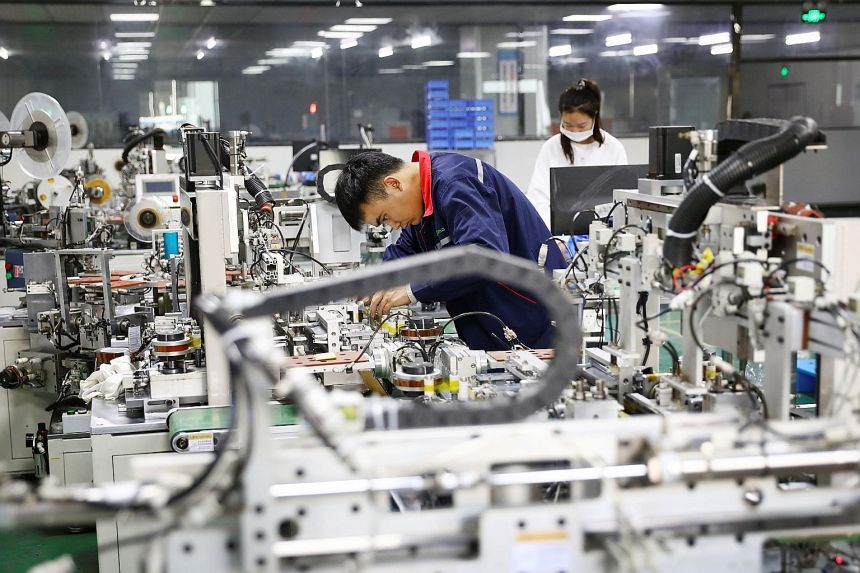 Employees in the workshop of a lithium battery manufacturing company in eastern China's Anhui province. The Caixin/Markit Manufacturing Purchasing Managers' Index rose to 54.9 last month from October's 53.6, the highest reading since November 2010. P