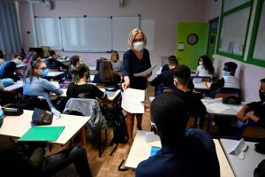 A teacher distributes documents to pupils in a classroom in Rennes, western France, on Sept 1, 2020.