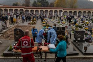 Red Cross workers examine a woman who felt ill during a Mass held to remember Covid-19 victims at a cemetery in the village of Nembro, Italy, on Nov 2, 2020.