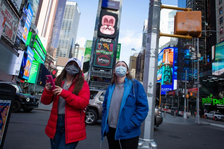 People wear face masks as they visit Times Square in New York on Dec 10, 2020.