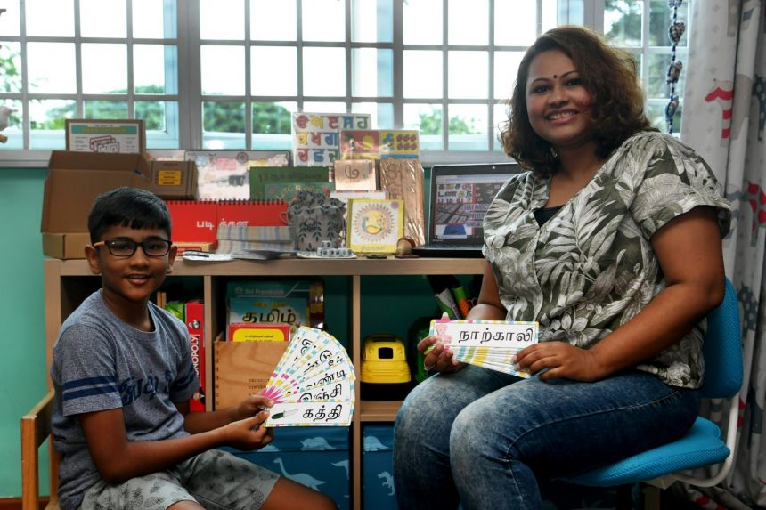 Ms Deepa Asha Dewi, 37, and her elder son Eswara Adhithiya, nine, with the Tamil flashcards she has made.