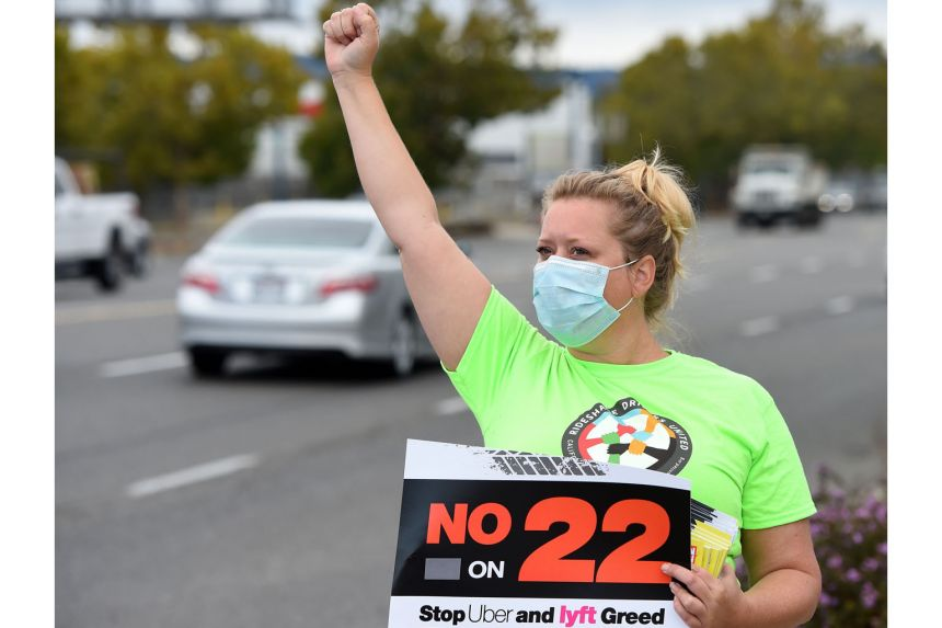 """Ride-sharing driver Erica Mighetto holding up a sign supporting a """"no"""" vote on Proposition 22 - a referendum to overturn a state law that would have forced gig firms to recognise their drivers as employees - in California in October last year. Califo"""