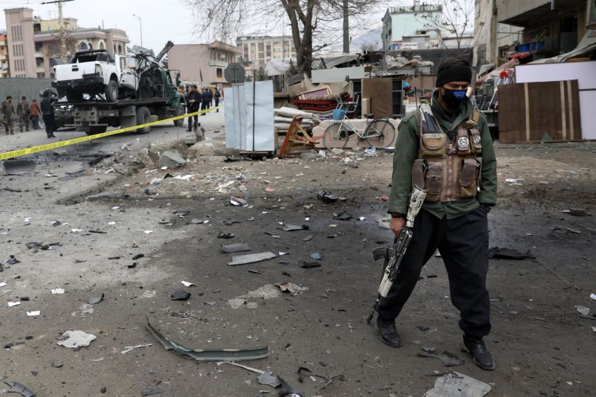 An Afghan security official inspects the scene of a bomb blast in Kabul, Afghanistan, Feb 20, 2021.