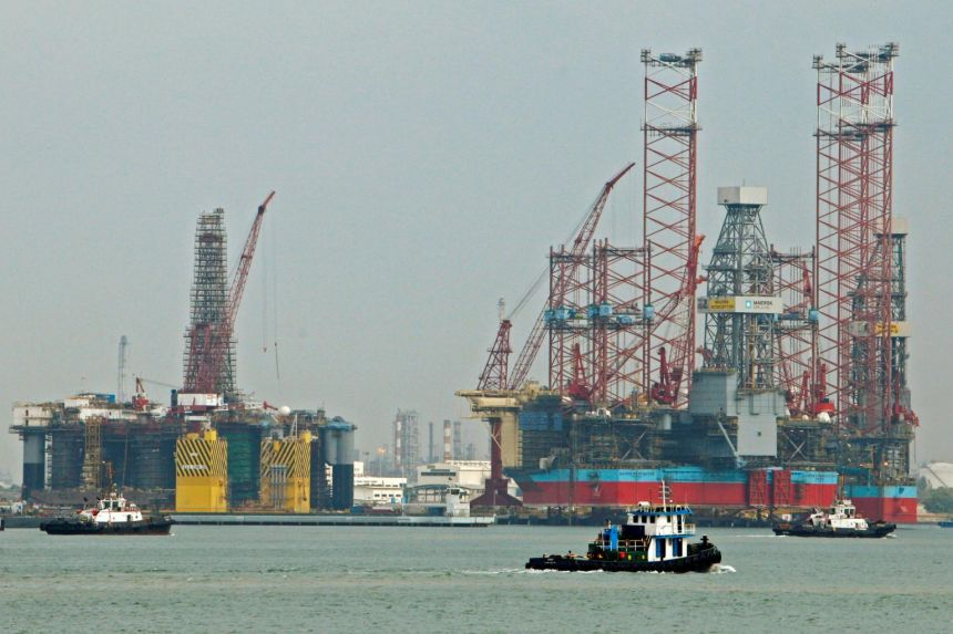 In a photo taken on Jan 21, 2014, tugboats pass jack-up rigs at a Keppel FELS shipyard in Singapore.