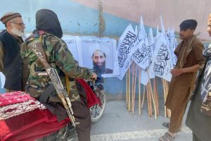 Taliban members standing near a poster of their leader Haibatullah Akhundzada in Kabul, on Aug 26, 2021.