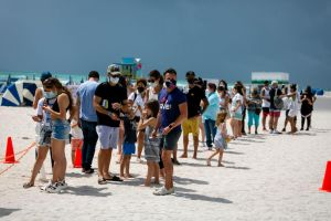 People wait in line to get the Johnson & Johnson vaccine at a pop-up vaccination booth in South Beach, Florida, on May 9, 2021.