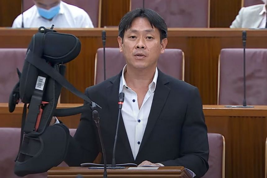 Mr Louis Ng (Nee Soon GRC) holding up a child's car seat in Parliament on May 11, 2021. He suggested providing one car seat for children aged nine months to four years, and another for those aged above four years.
