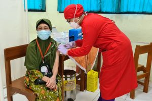 A medical worker inoculates an elderly woman with the Sinovac Covid-19 vaccine at a school in Jakarta.
