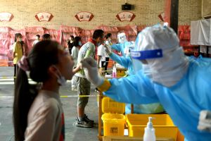 Medical workers take swabs from primary school students in Fuzhou, China, on Sept 15, 2021.